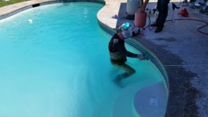 Man cleaning pool tile. Bay Area Pool Tile Cleaning